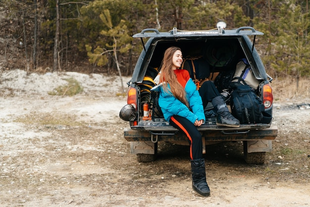 Młoda kobieta cieszy się naturę podczas gdy siedzący w samochodowym bagażniku