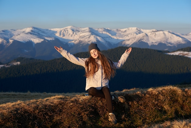 Młoda kobieta cieszy się ranku słońce w górach