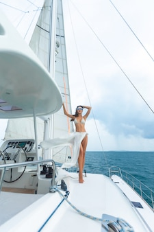 Młoda kobieta cieszy się słonecznych dni na żeglowanie jachcie w morzu.