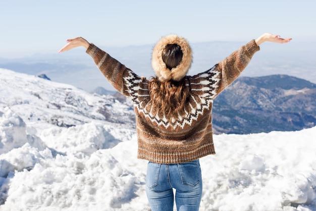 Młoda kobieta cieszy się śnieżne góry w zimie