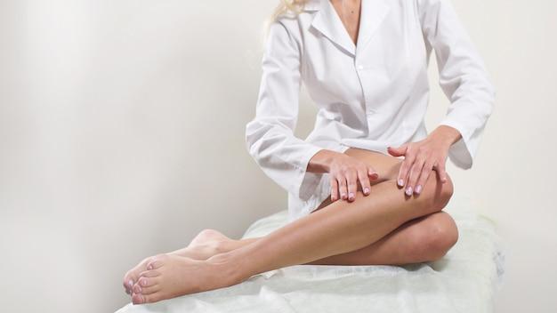 Młoda kobieta cieszy się zadbanymi gładkimi nogami po depilacji