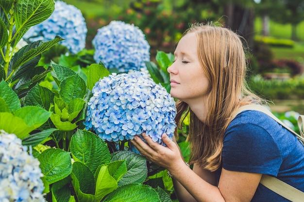 Młoda kobieta cieszy się zapachem hortensji.