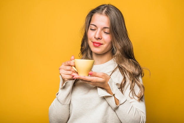 Młoda kobieta cieszy się zapachem jej świeżej kawy na żółtym tle