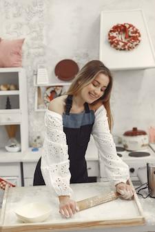 Młoda kobieta co ciasteczka w kształcie na boże narodzenie. salon ozdobiony dekoracjami świątecznymi w tle. kobieta w fartuchu.