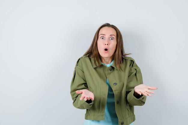 Młoda kobieta co gest zadawania pytań w t-shirt, kurtkę i patrząc zdziwiony, widok z przodu.