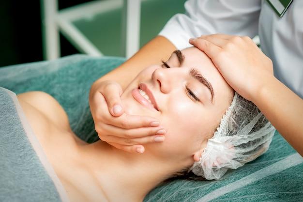 Młoda kobieta coraz masaż twarzy z zamkniętymi oczami przez kosmetyczkę w gabinecie kosmetycznym