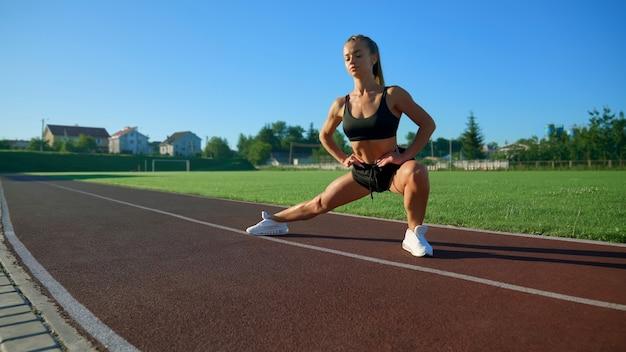 Młoda kobieta ćwicząca rzuty boczne na stadionie