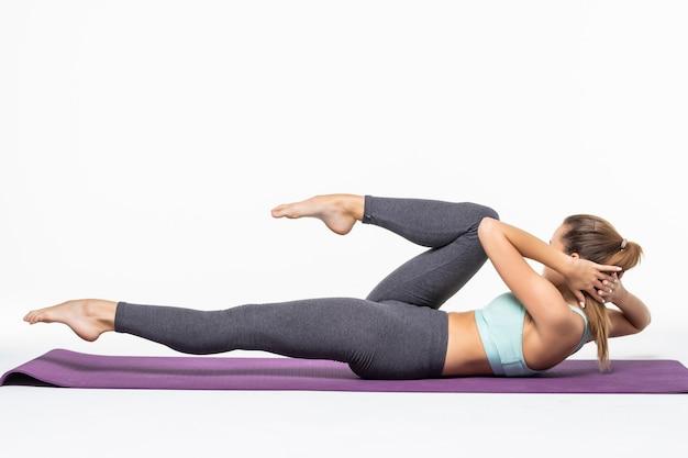 Młoda kobieta ćwiczeń i robi crunch do pracy jej abs na białym tle