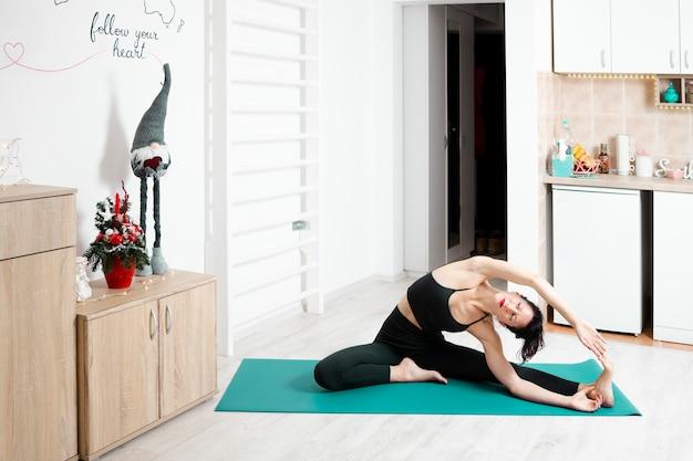 Młoda kobieta, ćwiczenia jogi we własnym mieszkaniu i ciesząc się jej dniem