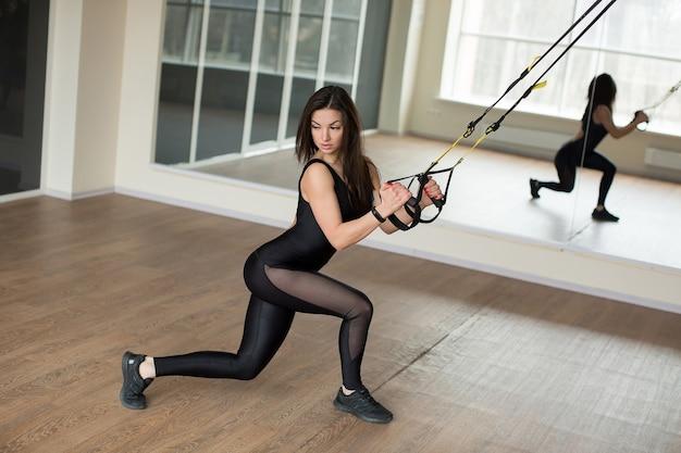 Młoda kobieta ćwiczenia pompki treningowe z trx fitness pasy na siłowni trening sportowy concept zdrowego stylu życia.