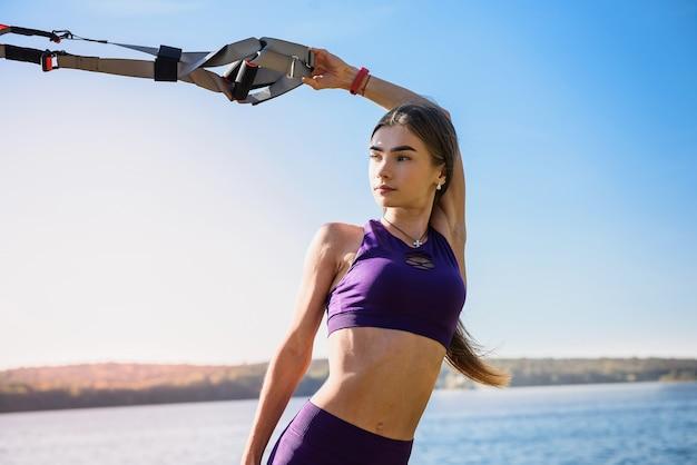 Młoda kobieta ćwiczenia z zawiesiem trenera w parku, w pobliżu jeziora.
