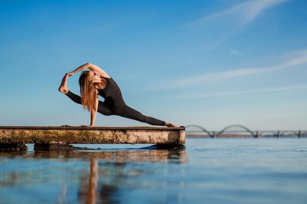 Młoda kobieta ćwiczy ćwiczenia jogi przy cichym drewnianym molo z miastem sport i rekreacja w pośpiechu miasta