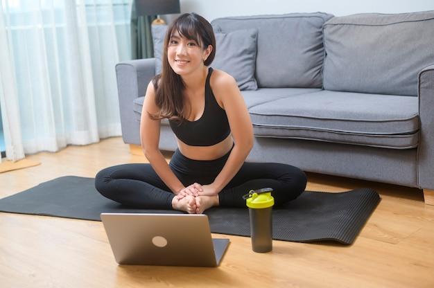 Młoda kobieta ćwiczy i ogląda zajęcia fitness online na laptopie w salonie w domu, sport, fitness i koncepcja technologii.