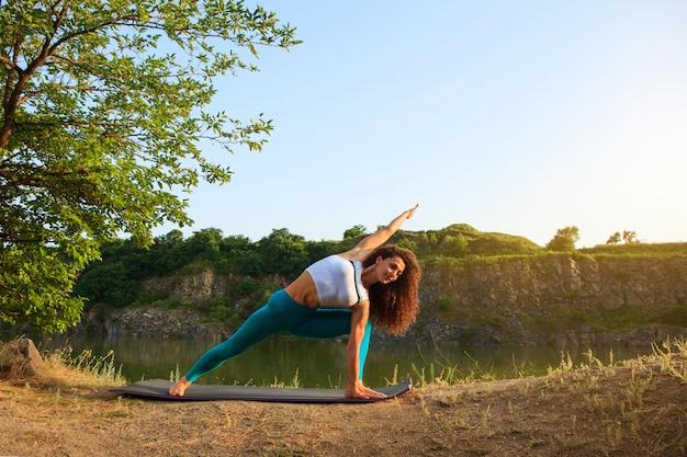 Młoda kobieta ćwiczy joga blisko rzeki