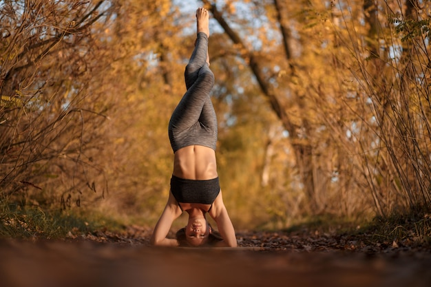 Młoda kobieta ćwiczy joga ćwiczenie przy jesień parkiem z żółtymi liśćmi. sport i rekreacja w stylu życia