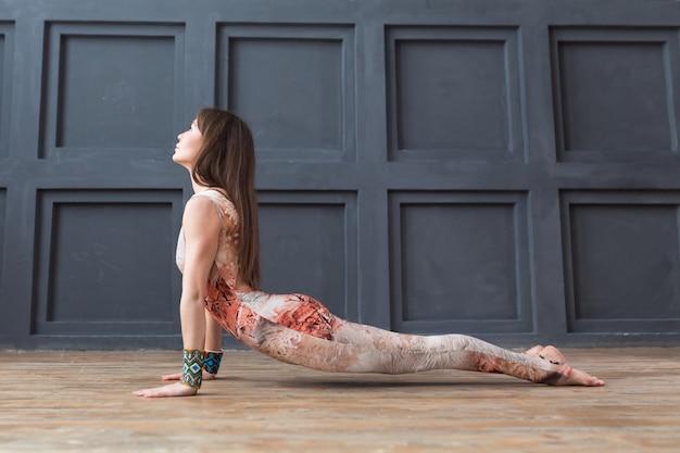 Młoda kobieta ćwiczy joga kobry pozę