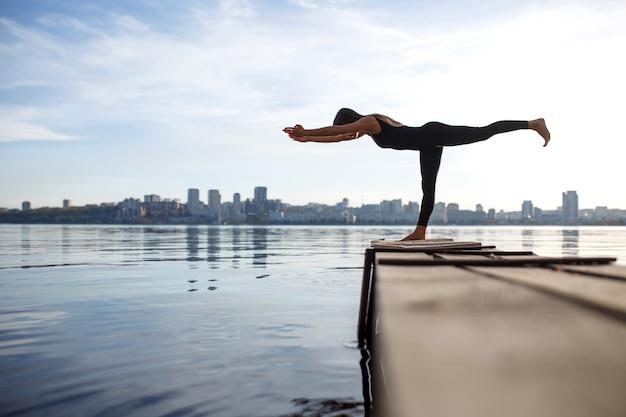 Młoda kobieta ćwiczy jogę ćwiczy przy spokojnym drewnianym molem z miastem. sport i rekreacja w ruchu miejskim