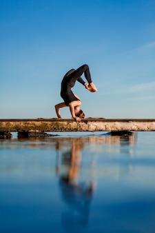 Młoda kobieta ćwiczy jogę ćwiczy przy spokojnym drewnianym molem z miastem