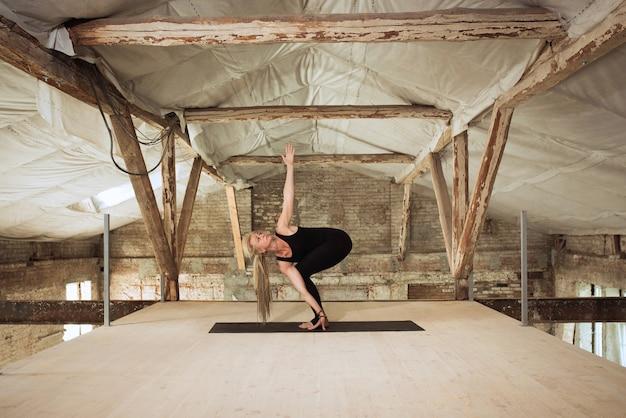 Młoda kobieta ćwiczy jogę na opuszczonej budowie