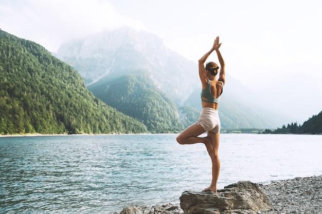Młoda kobieta ćwiczy jogę nad górskim jeziorem dziewczyna ćwiczy jogę na łonie natury zdrowy styl życia