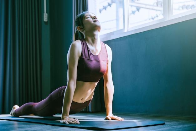 Młoda kobieta ćwiczy jogę w klasie; piękna dziewczyna czuje spokój i odpoczywa na zajęciach jogi