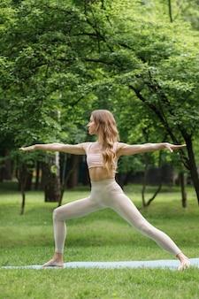 Młoda kobieta ćwiczy jogę w parku latem