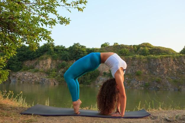 Młoda kobieta ćwiczy jogę w pobliżu rzeki