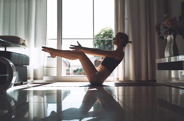 Młoda kobieta ćwiczy jogę w pomieszczeniu piękna dziewczyna medytuje i robi pozy jogi w domu