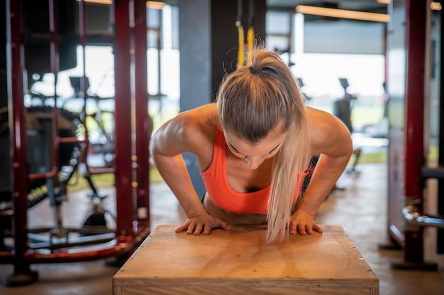 Młoda kobieta ćwiczy korby na drewnianych skrzynkach w gym