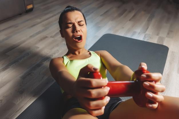 Młoda kobieta ćwiczy mocno z dumbbells w domu