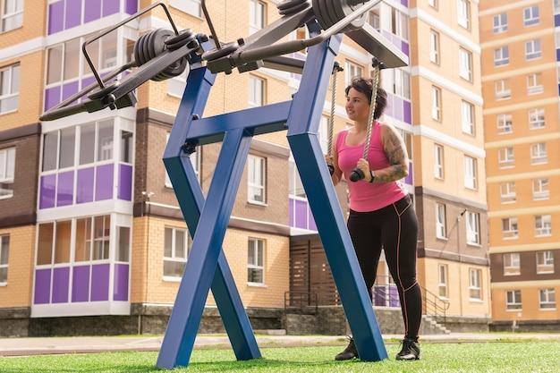 Młoda kobieta ćwiczy na maszynie do masy ulicznej na zewnątrz na dziedzińcu miasta