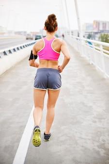 Młoda kobieta ćwiczy na świeżym powietrzu. kobieta, jogging wczesnym rankiem