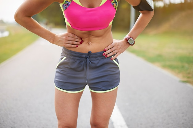 Młoda kobieta ćwiczy na świeżym powietrzu. kolka to częsty problem podczas biegania