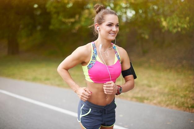 Młoda kobieta ćwiczy na świeżym powietrzu. lato pomaga w zdobyciu motywacji