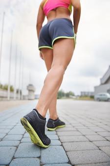 Młoda kobieta ćwiczy na świeżym powietrzu. ludzkie nogi przed ciężkim treningiem