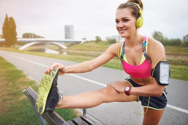 Młoda kobieta ćwiczy na świeżym powietrzu. najpierw rozgrzewka, potem ciężki trening