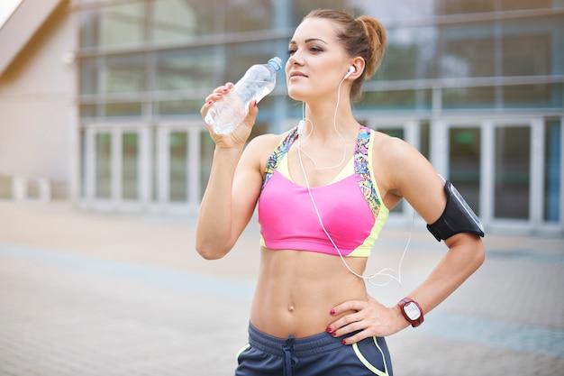 Młoda kobieta ćwiczy na świeżym powietrzu. nasz organizm musi być cały czas nawilżany