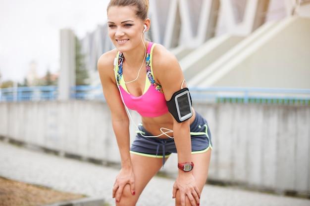 Młoda kobieta ćwiczy na świeżym powietrzu. po krótkim rozciąganiu jestem gotowy do biegu