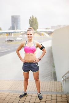 Młoda kobieta ćwiczy na świeżym powietrzu. portret kobiety jogger stojącej na schodach