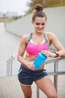 Młoda kobieta ćwiczy na świeżym powietrzu. sportowa kobieta trzyma butelkę pełną białek