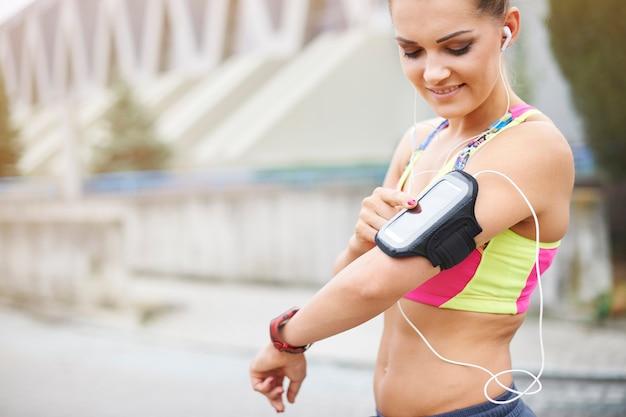 Młoda kobieta ćwiczy na świeżym powietrzu. ten gadżet jest bardzo pomocny podczas biegania