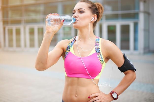 Młoda kobieta ćwiczy na świeżym powietrzu. woda jest bardzo ważna w codziennej diecie