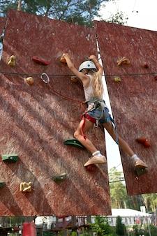 Młoda kobieta ćwiczy pięcie na rockowej ścianie indoors