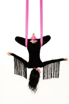 Młoda kobieta ćwiczy powietrzną jogę antygrawitacyjną z inną inwersją z hamakiem