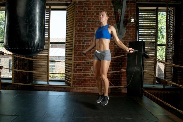 Młoda kobieta ćwiczy skakanie na skakance