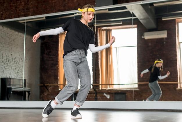 Młoda kobieta ćwiczy taniec przed lustrem