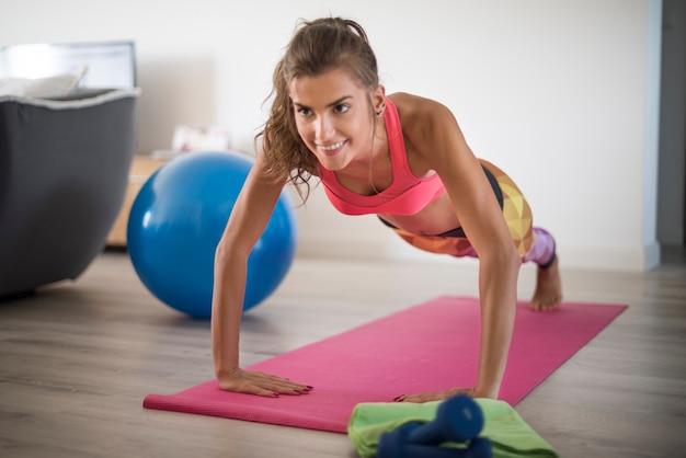 Młoda kobieta ćwiczy w domu. ta kobieta ma niesamowitą wytrzymałość