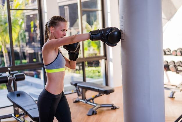 Młoda kobieta ćwiczy w gym na worek treningowy