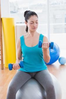 Młoda kobieta ćwiczy z dumbbells na sprawności fizycznej piłce