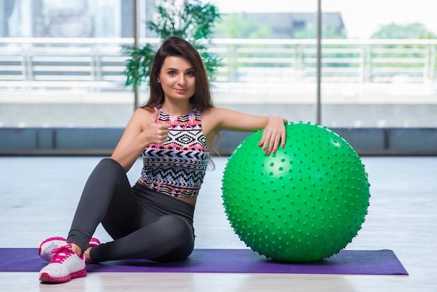 Młoda kobieta ćwiczy z szwajcarską piłką w zdrowia pojęciu